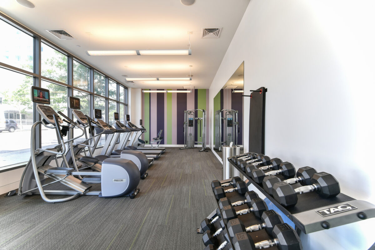 One of two fitness centers with elliptical and cardio machines, strength training equipment, and free weights
