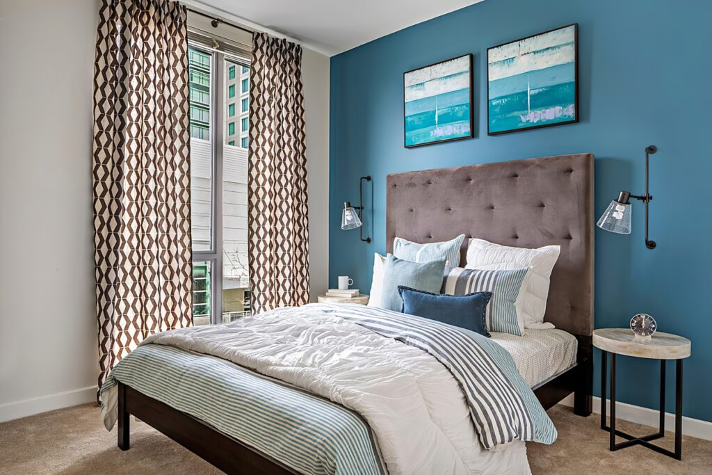 Carpeted and furnished model apartment bedroom with queen bed, blue painted walls, built-in lighting fixtures, and window with blinds