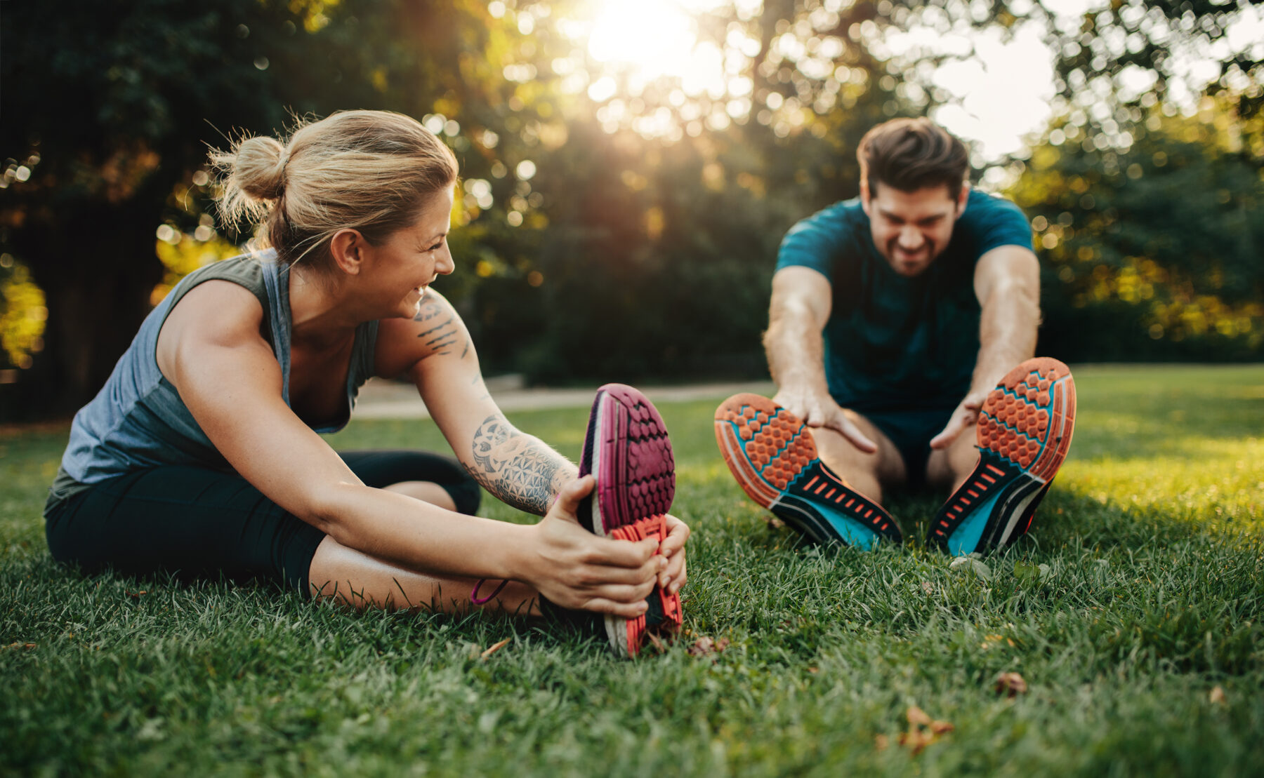 Male and female human sitting on lawn stretching in exercise clothing.