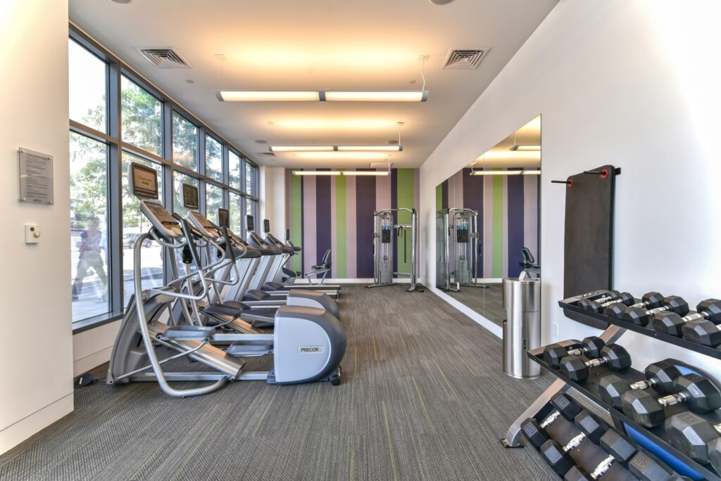 Fitness center area with elliptical machines mirrors, weights and weight machine