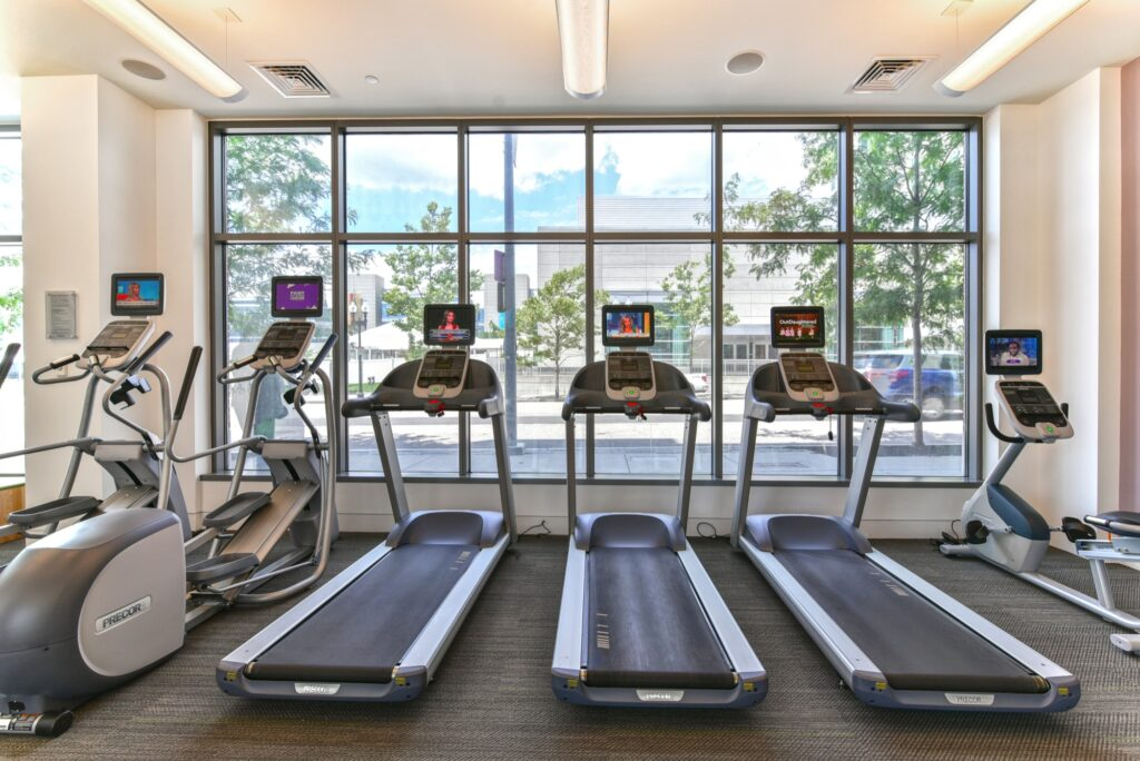 Fitness center area with elliptical machines, punching bag, treadmills and windows with street view