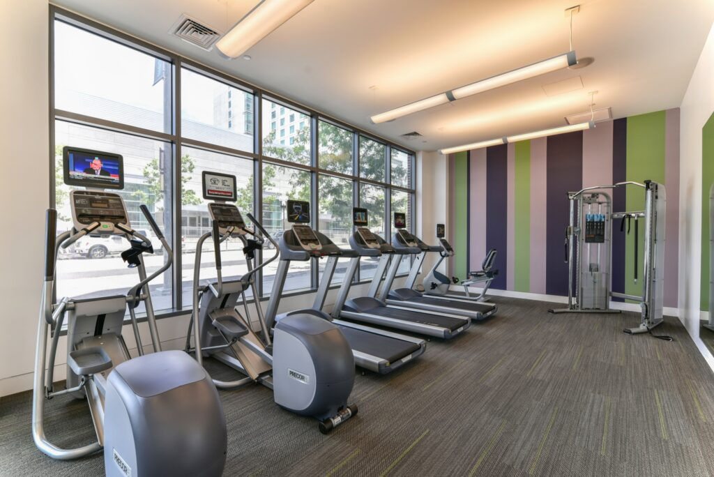 Fitness center area with elliptical machines, punching bag, treadmills and windows with street view and weight machine