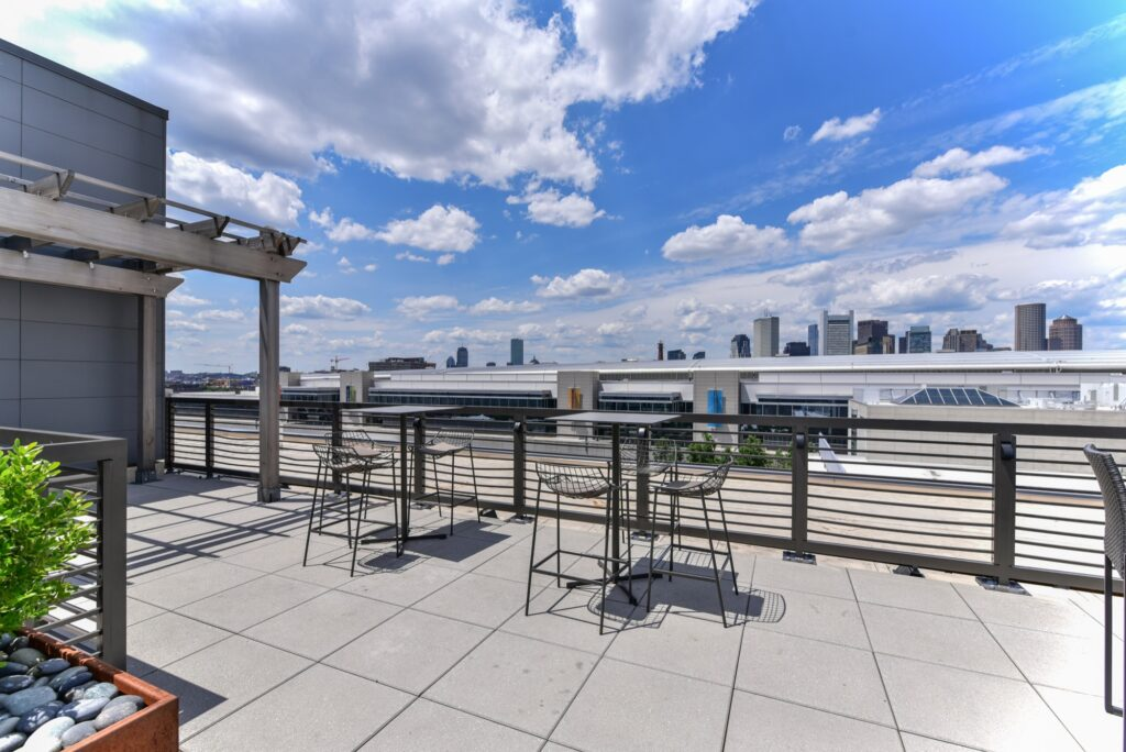 Rooftop clubroom area with community seating, tables and city view of downtown