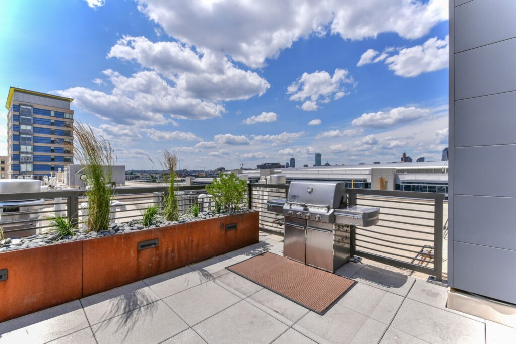 Rooftop clubroom area with community lounge seating, tables and city view and grille