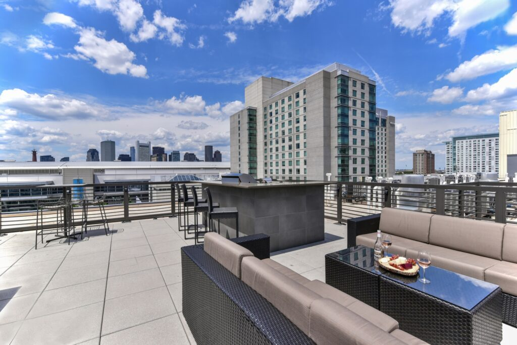 Rooftop clubroom area with community lounge seating, tables and city view with set table and large building looming in the background