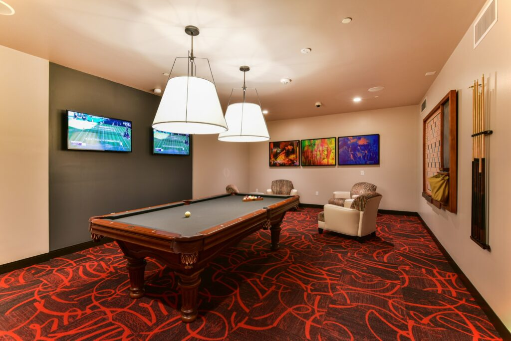 Community game room billiards table with tiles red carpet, and wall mounted TV
