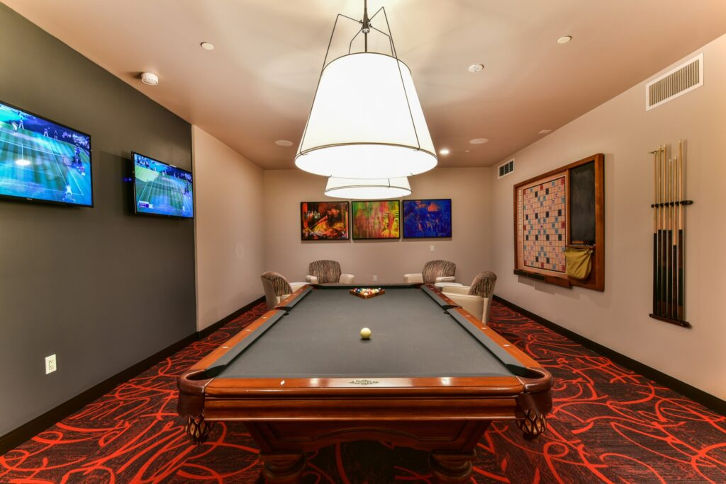Community game room billiards table with tiles red carpet, and wall mounted TV and prominent lamps
