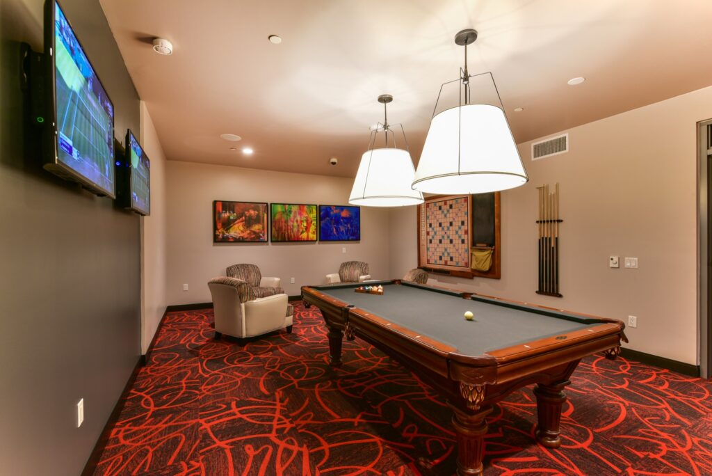 Community game room billiards table with tiles red carpet, and wall mounted TV and seating
