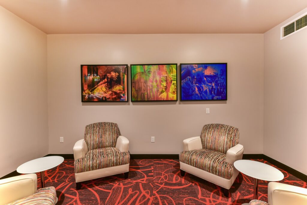 Community room tiles red carpet, and wall mounted modern art in front of modern seating
