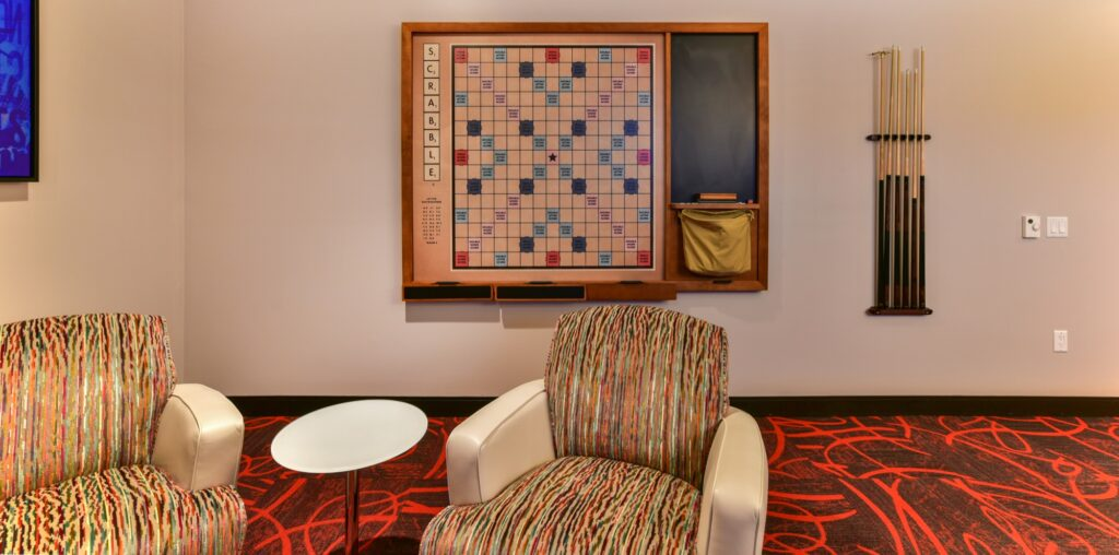Community game room with red carpet, and wall mounted games in front of modern seating