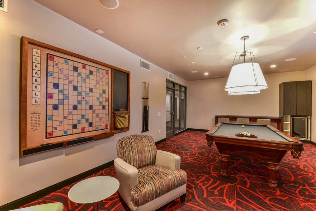 Community game room with red carpet, and wall mounted games in front of modern seating facing an exit