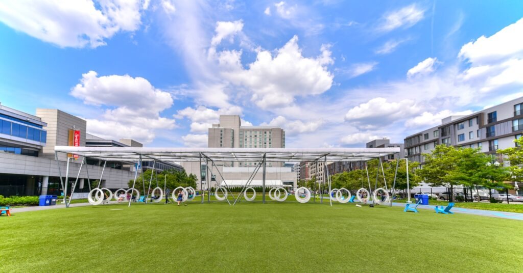 Wide angle view of The Lawn on D community field and recreation area with modern swings and ample green space for outdoor activities and pets
