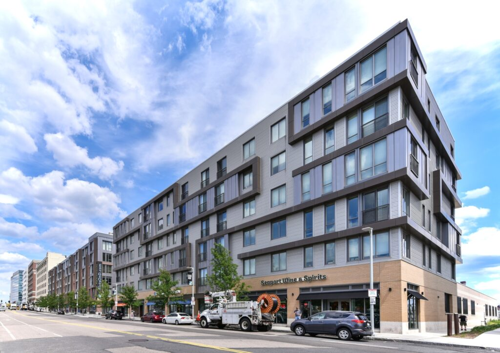 Exterior of Flats on D midrise apartment building facing South Boston street with onsite retail, bike racks, and cars parked in front
