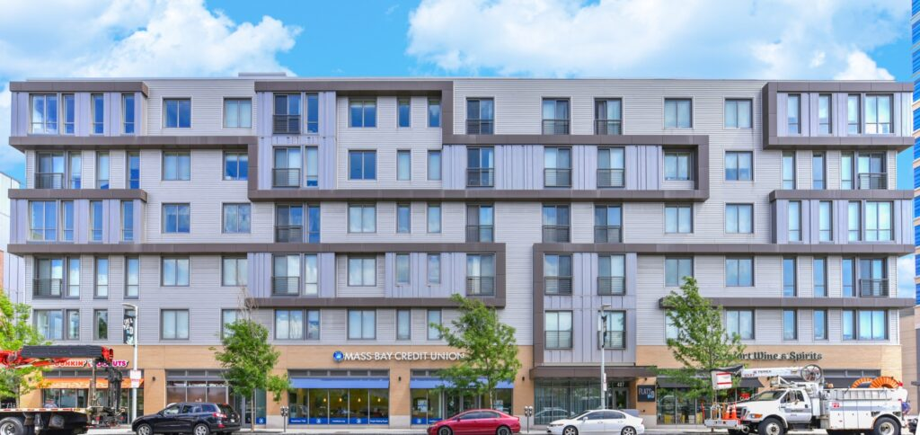Exterior of Flats on D apartment building facing South Boston street with onsite retail, bike racks, and public transportation stops