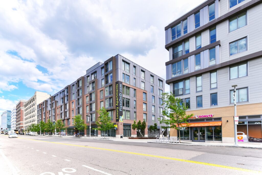 Exterior of Flats on D midrise apartment building facing South Boston street with onsite retail, bike racks, and Dunkin Donuts