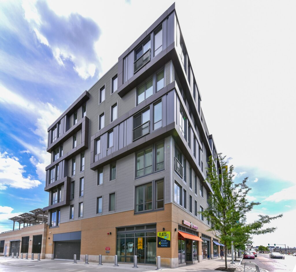 Exterior of Flats on D midrise apartment building facing South Boston street with onsite retail and sign.