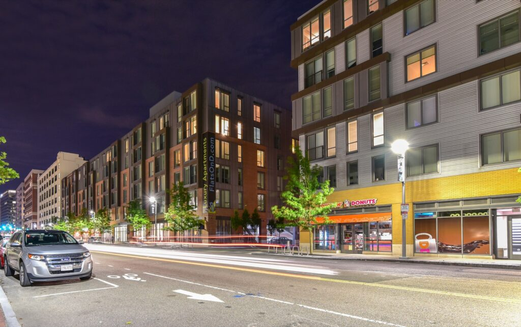 Exterior of Flats on D midrise apartment building facing South Boston street with onsite retail, bike racks, and Dunkin Donuts at night