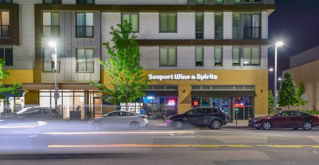 Seaport Wine and Spirits building business sign at night with apartment living above