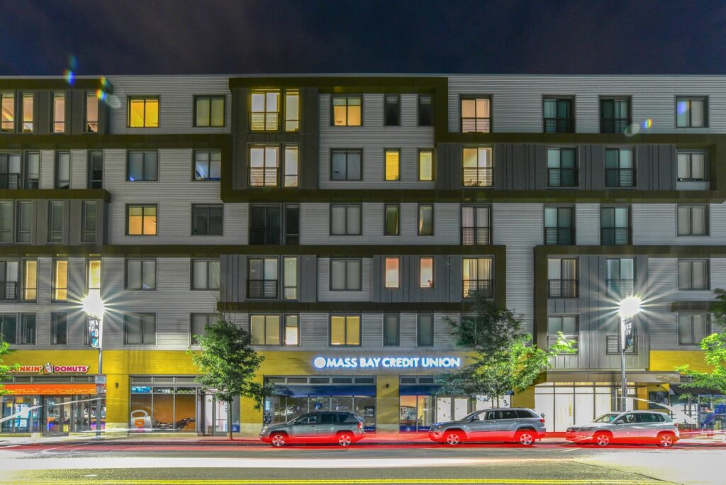 Long exposure shot of cars passing in front of businesses at night with apartment living above
