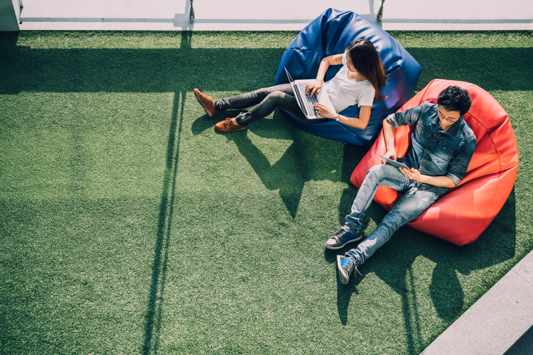 Young Asian couple using laptop notebook and digital tablet together in modern public park, sit on bean bag, top view with copy space on grass