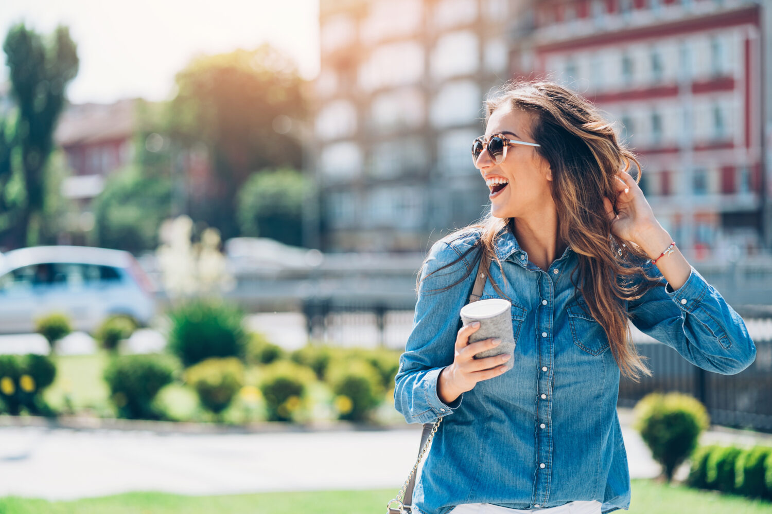 Cheerful young woman holding coffee in the city neighborhood