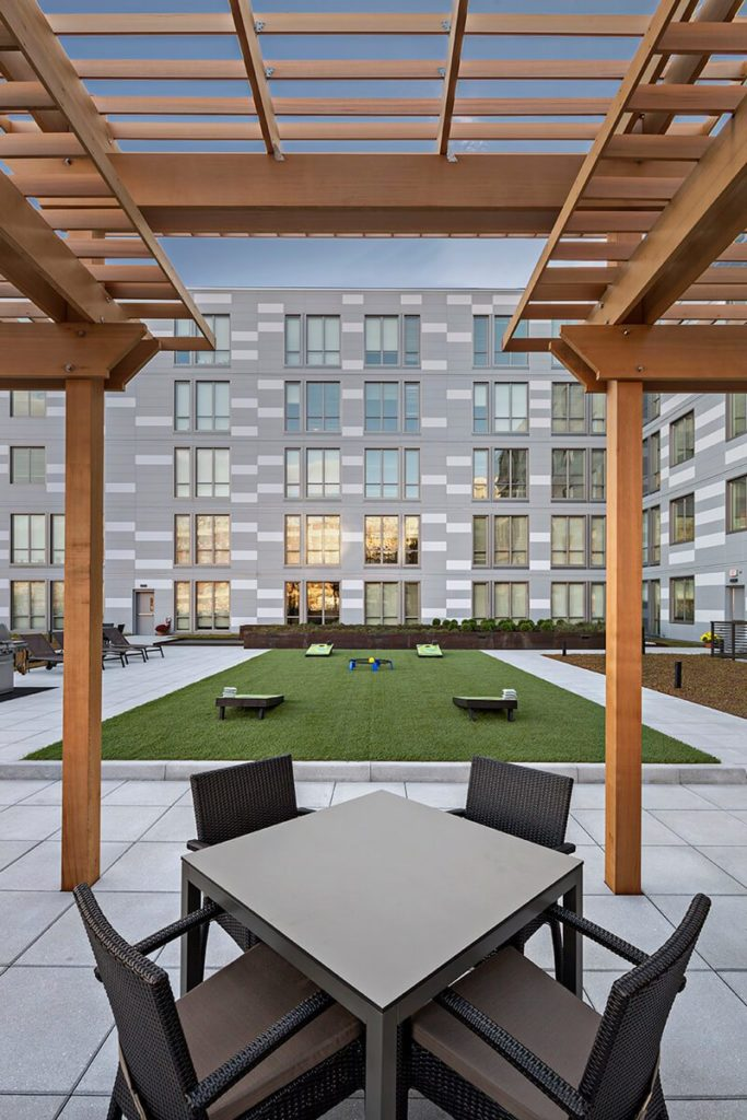 Community rooftop courtyard with turf lawn and covered patio seating