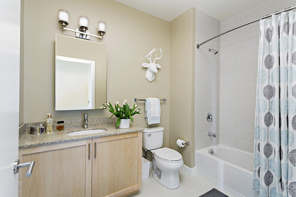 Model apartment bathroom with granite countertop, natural wood cabinets, single sink, and tub shower