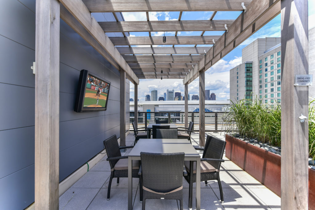 Rooftop terrace with covered seating, skyline views of Boston, and TV