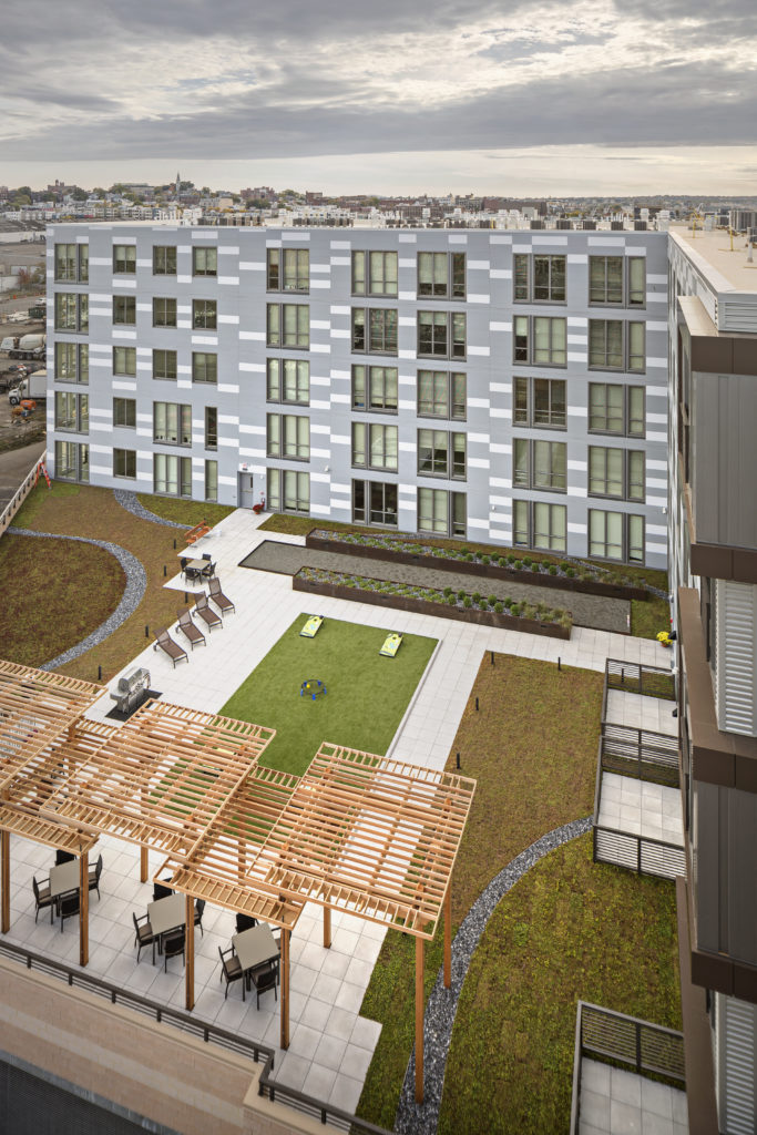 Aerial view of apartment building exterior and rooftop deck with landscaped lawn and gaming turf