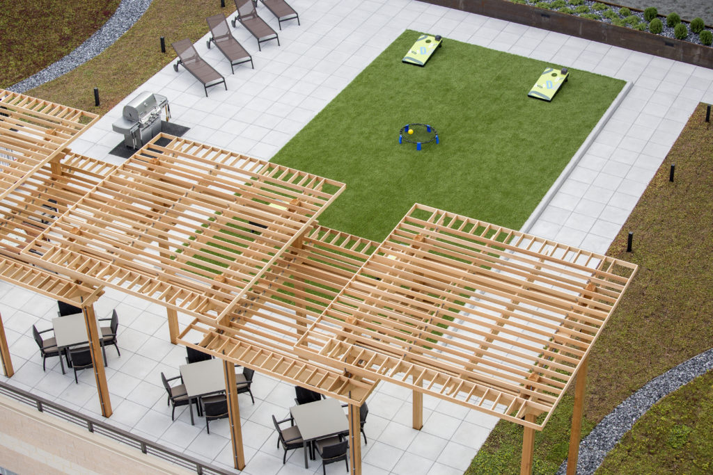 Aerial view of roof deck with covered patio seating, barbecue grills, and turf lawn with bag toss games