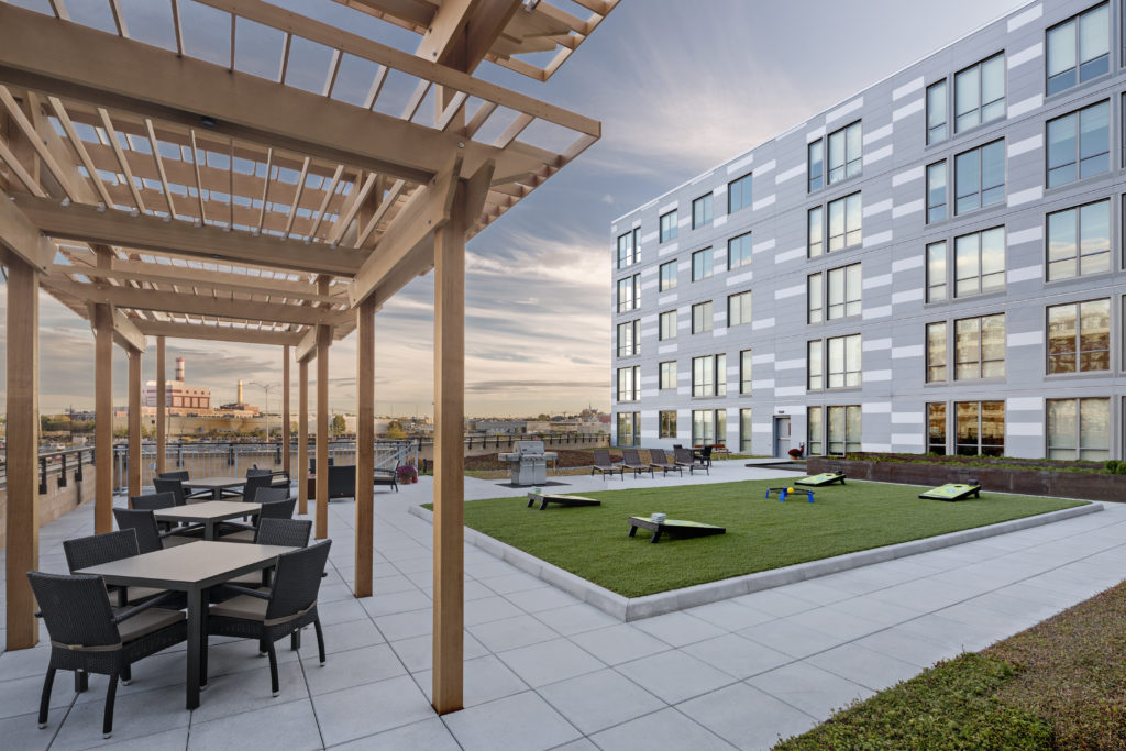 Community rooftop terrace with covered patio lounge seating, gas grills and bag toss games