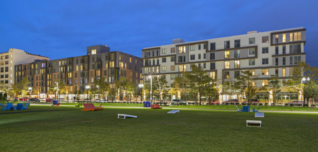Exterior view of apartment building at dusk with open grass lawn with lounge chairs and bag toss games