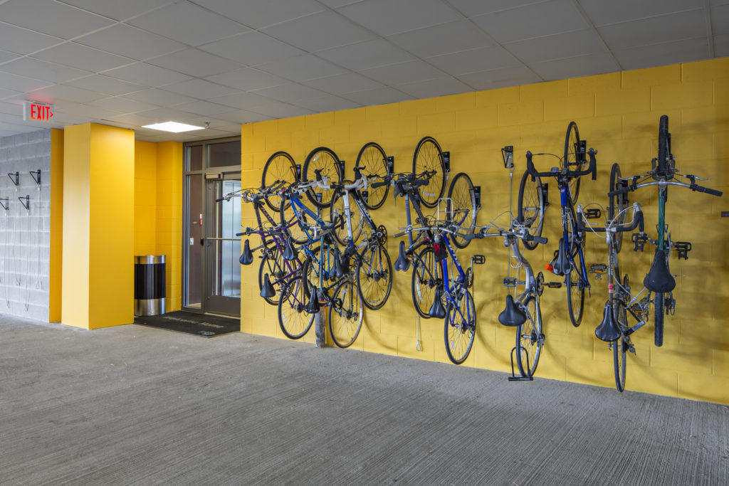 Bicycles mounted on the wall inside of Flats on D apartment parking garages near building entrance.