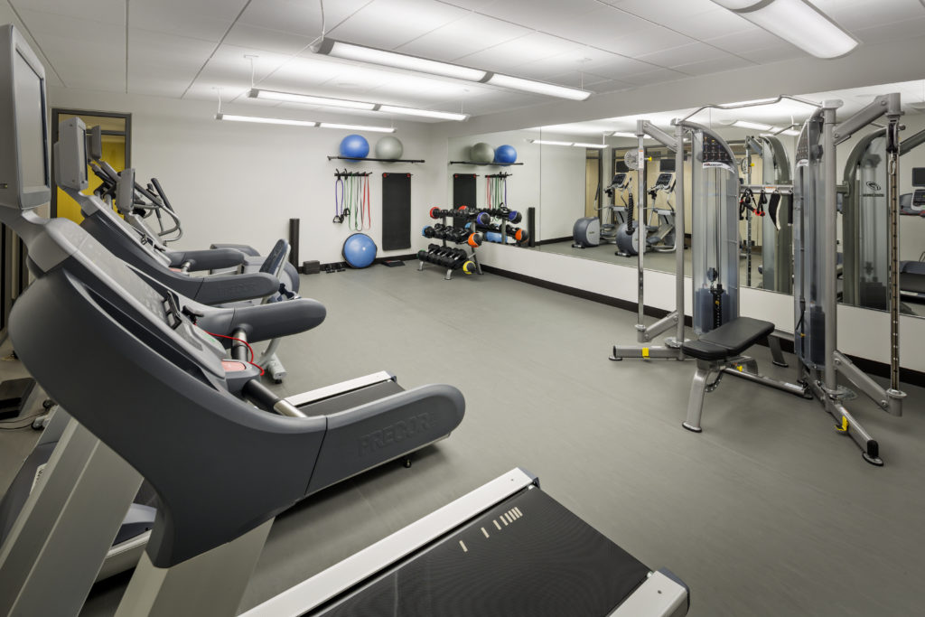 24-hour fitness center with cardio machines, strength training equipment, and free weights with large mirror.