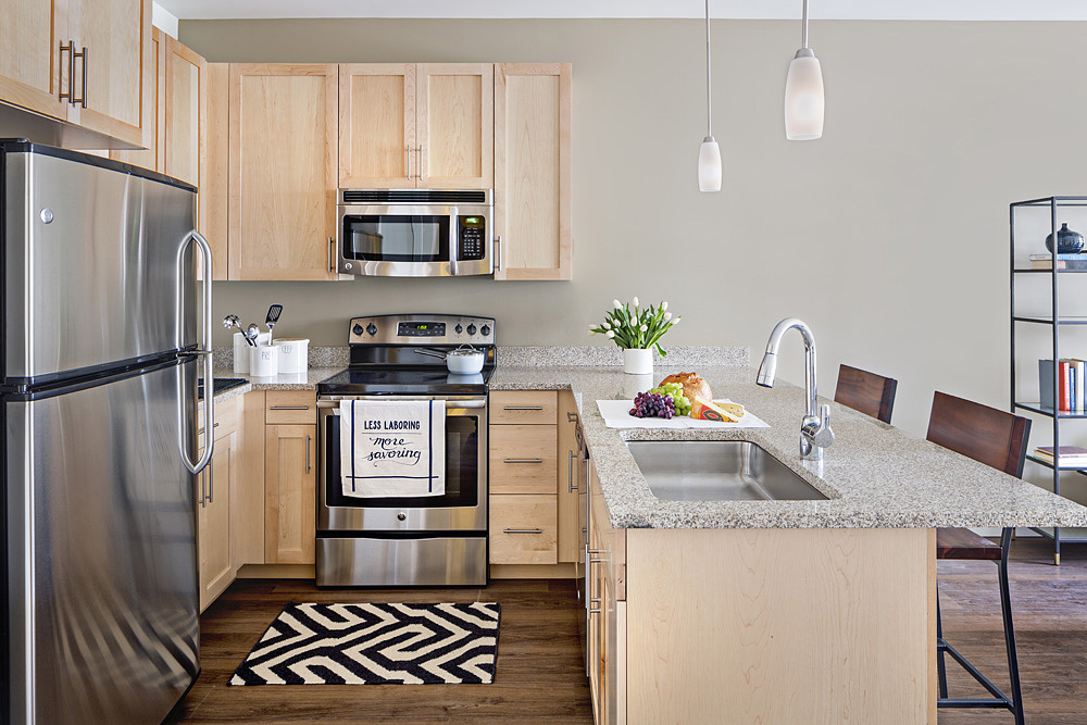 Interior of model apartment kitchen with stainless steel fridge, microwave, oven, sink, and dishwasher