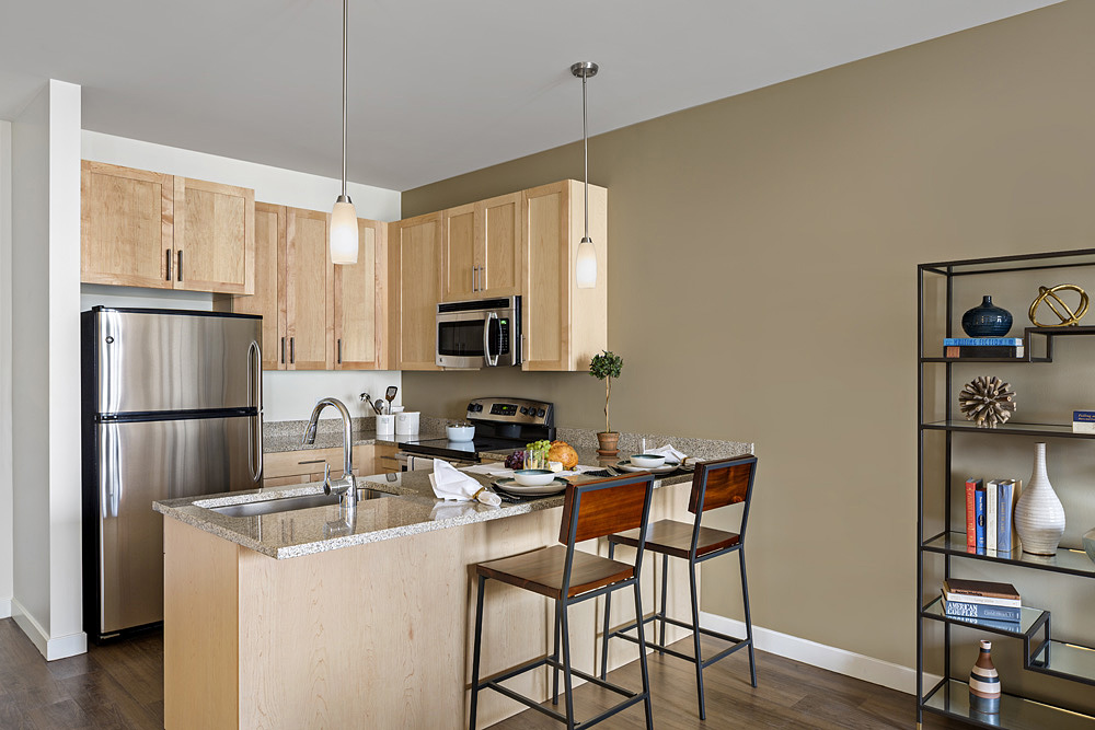 Interior of model apartment kitchen with pendant lighting, stainless steel appliances, countertop seating and deep sink