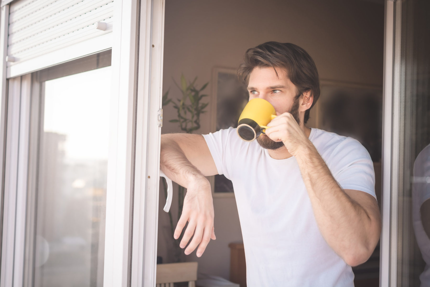 Man standing at apartment balcony looking out the window and drinking coffee