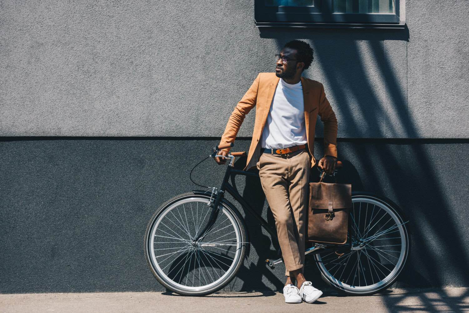 Man standing by wall near bicycle and looking away holding a bag